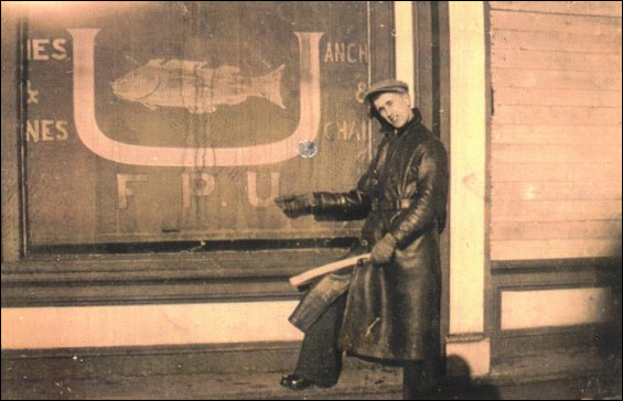 Randolph Tulk pointing to the FPU insignia embossed on the Fishermen's Union Trading Company store blind at Port Union.