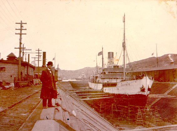 "A man observing the vessel ""Beothic"" on dry dock in the west end of St. John's harbour"