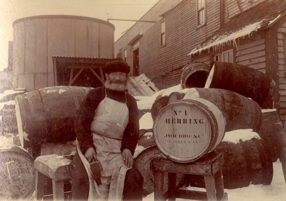 A cooper standing with Job Brothers & Co. herring barrels