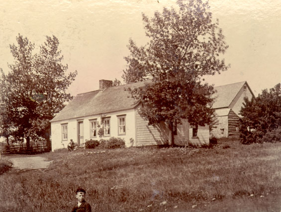 Boy in front of a farm house
