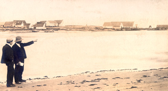 Two men on Blanc Sablon beach looking towards Job Brothers & Co. premises