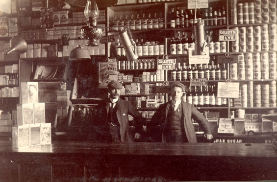 Two men standing at a counter inside a grocery store