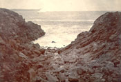 Unidentified rocky beach with ocean view and iceberg in background