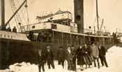 "Seven men and two women standing near the S.S. ""Sagona"""