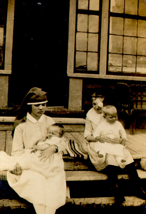A nurse and three injured children sitting on the front steps of the St. Anthony hospital