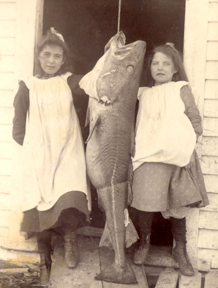 Two young girls with a large codfish.