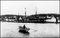 "Boy rowing boat at Battle Harbour with the ""Southern Cross"" at the wharf"