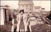 Elizabeth Feltham. Dilapidated house behind her was owned by Carrie King who left Deer Island for the U.S. after her husband was drowned in the schooner Little Jepp</em.