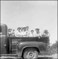 Group of women in a pickup truck during the construction of the Road from Harbour Buffett to Kingwell, Placentia Bay.